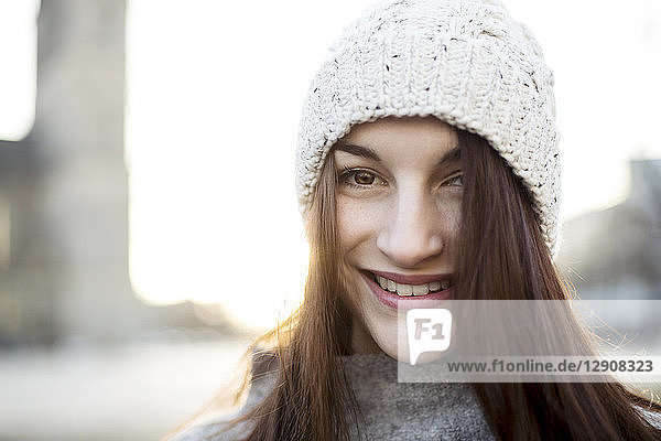 Portrait of content young woman wearing woolly hat in winter