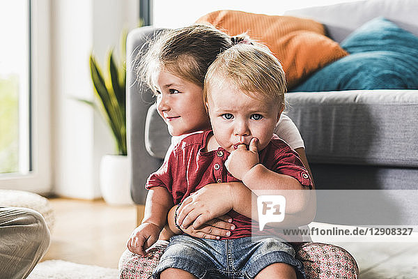 Brother and sister at home in living room