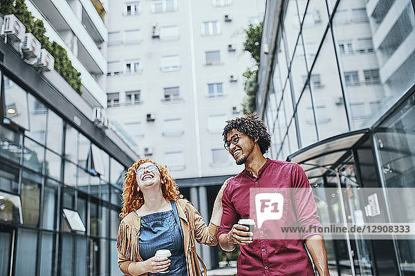 Colleagues walking together in the city  woman drinking coffee