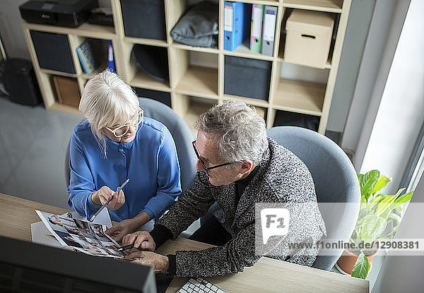 Two senior colleagues working together at desk in office discussing photos