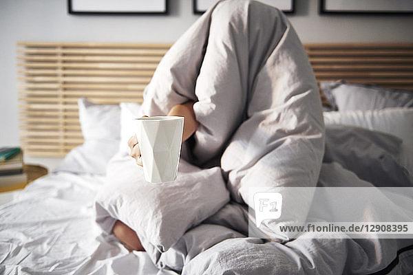 Woman hidden under blanket demanding coffee