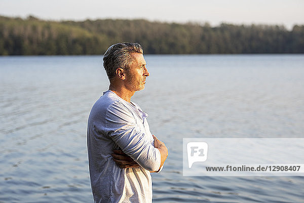 Pensive man standing at lake looking at distance