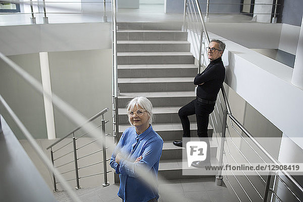 Two senior colleagues standing on office stairs