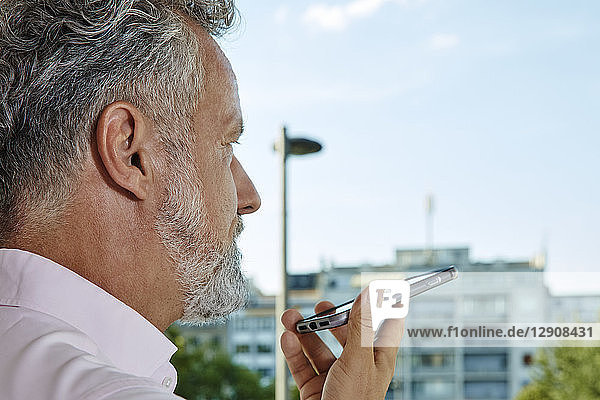 Close-up of mature man using smartphone outdoors