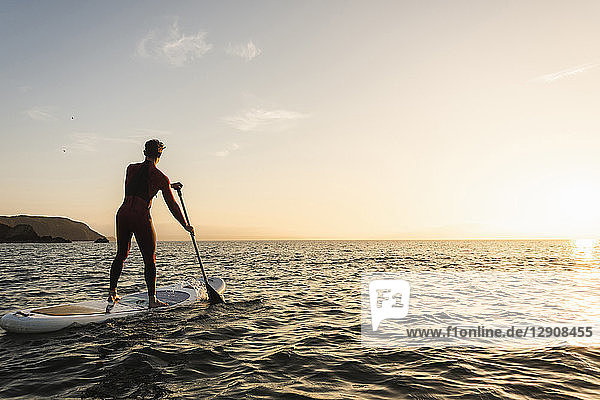 Young man on paddleboard at sunset