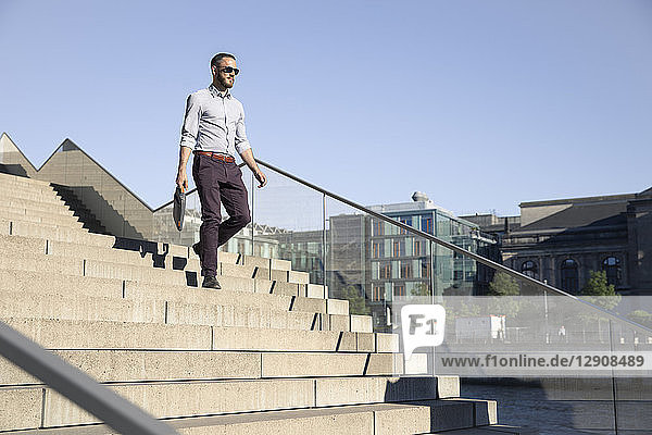 Businessman wearing sunglasses walking downstairs