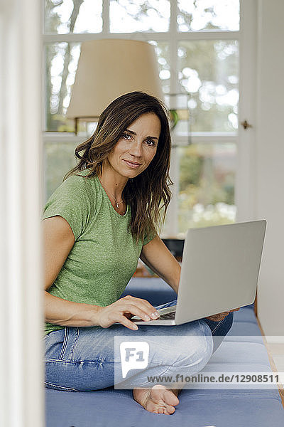 Portrait of confident mature woman sitting on couch at home with laptop