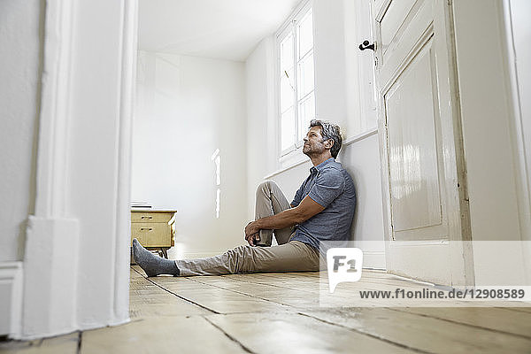 Mature man sitting on floor of his bedroom  daydreaming