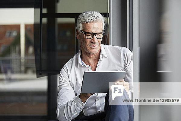 Serene businessman sitting on ground in office  using digital tablet