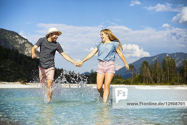 Young couple holding hands and running through water