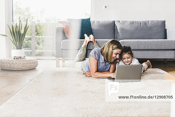 Mother and daughter using laptop  lying on carpet
