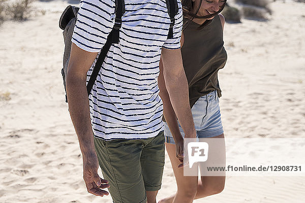 Young couple walking on the beach  holding hands