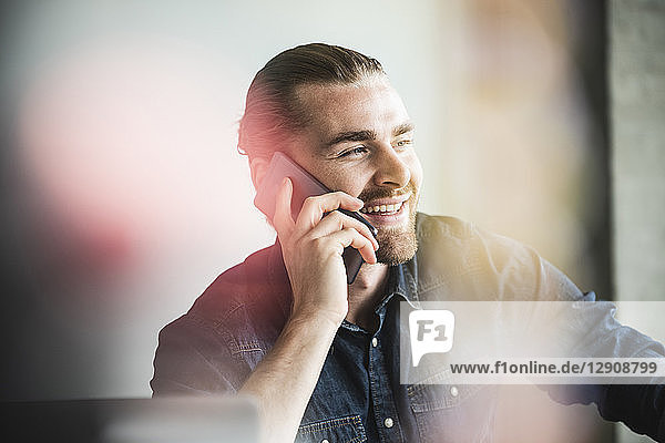Portrait of smiling young businessman on cell phone in office