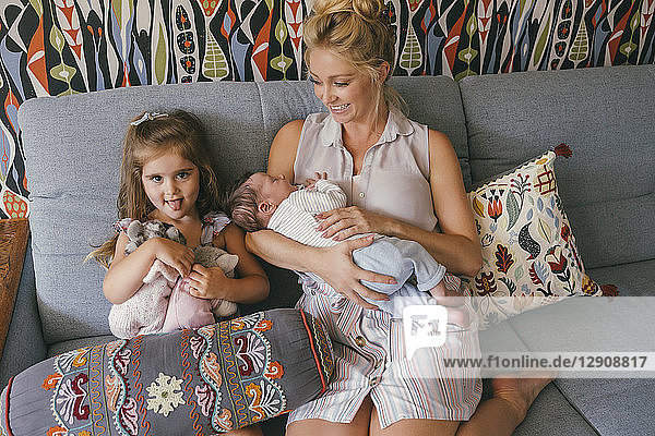 Smiling mother sitting on couch with newborn baby and daughter