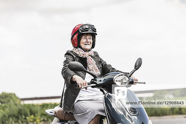 Active senior lady riding motor scooter on the road