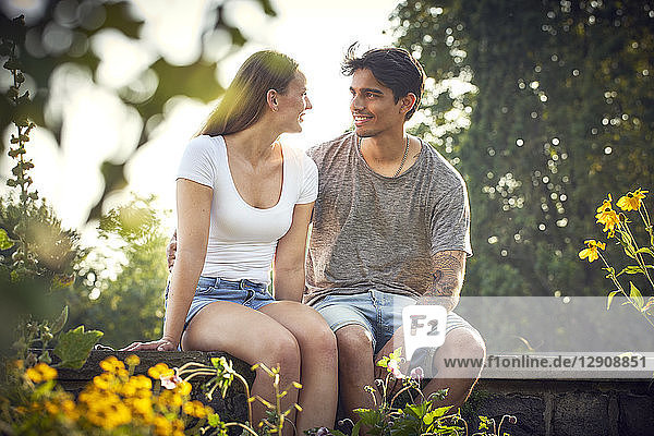 Romantic young couple sitting on wall in a park  with arms around