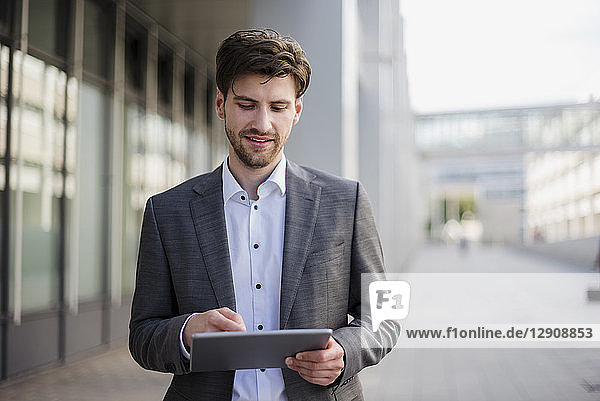 Smiling businessman in the city using tablet