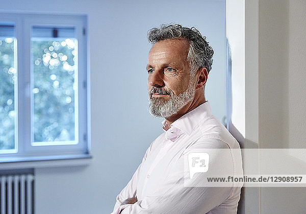 Portrait of mature man leaning against doorframe in office thinking
