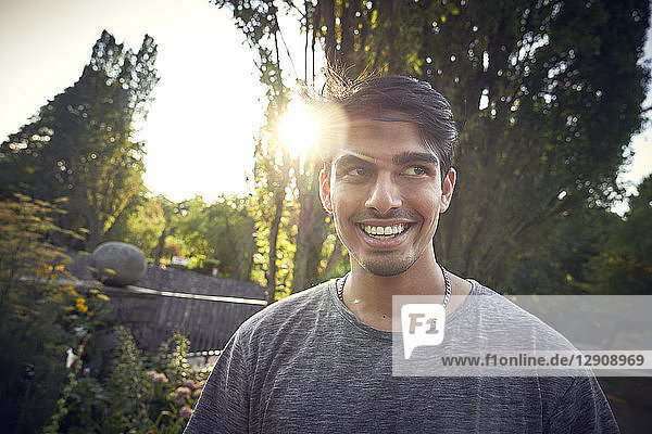 Portrait of a young man in a park at sunset  smiling