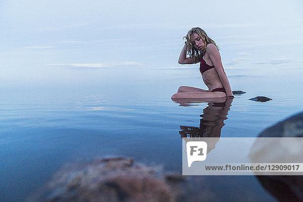 Young woman wearing bikini  sitting on a stone in a lake