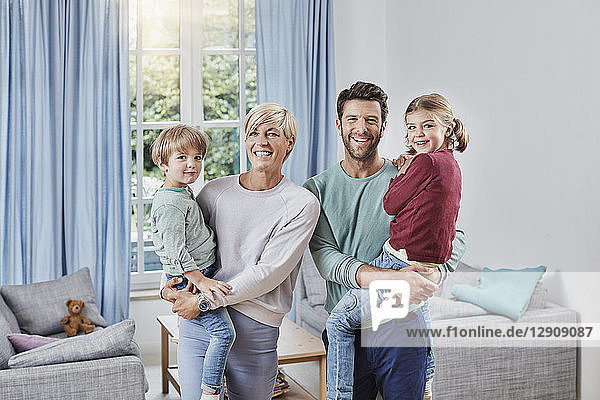 Portrait of happy family with two kids at home