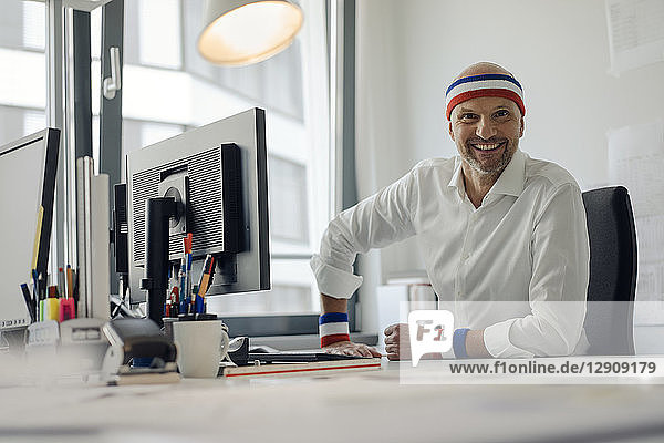 Businessman sitting in office  wearing sweat bands
