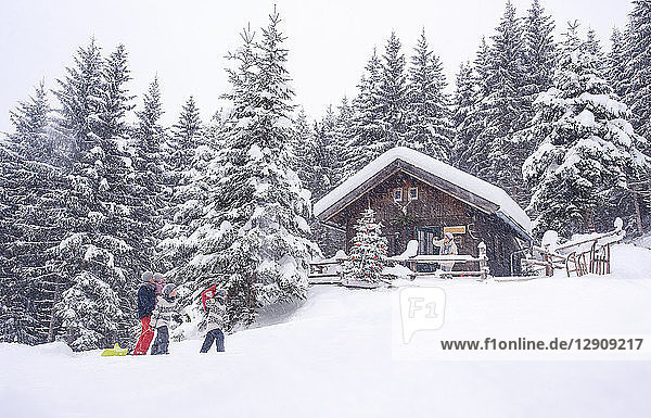 Austria  Altenmarkt-Zauchensee  family with sledges at wooden house at Christmas time