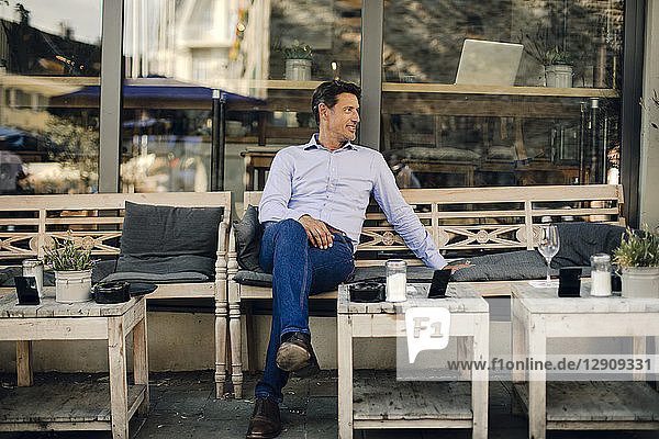 Businessman sitting in coffee shop  smiling