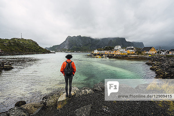 Norway  Lofoten  rear view of man standing at the coast