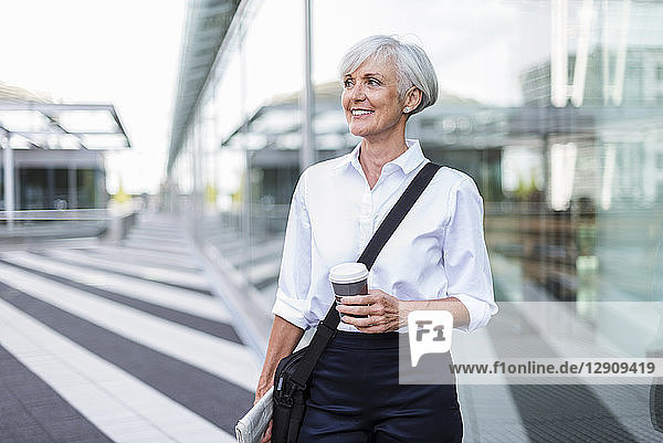 Smiling senior businesswoman in the city on the go