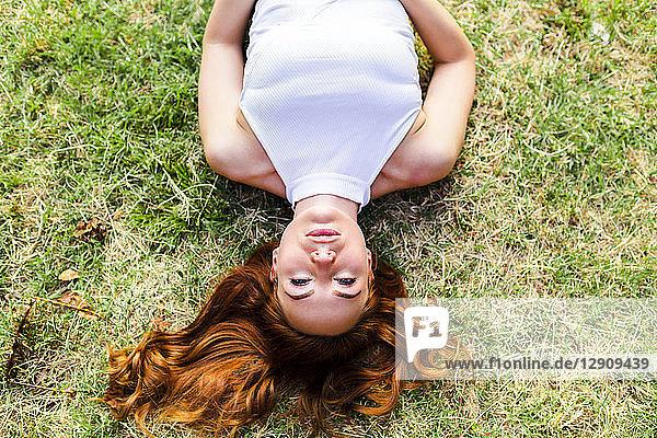 Portrait of redheaded woman lying on a meadow