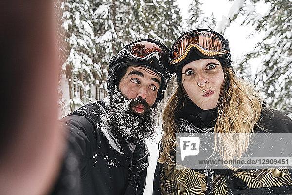 Selfie of happy couple in skiwear grimacing in winter forest
