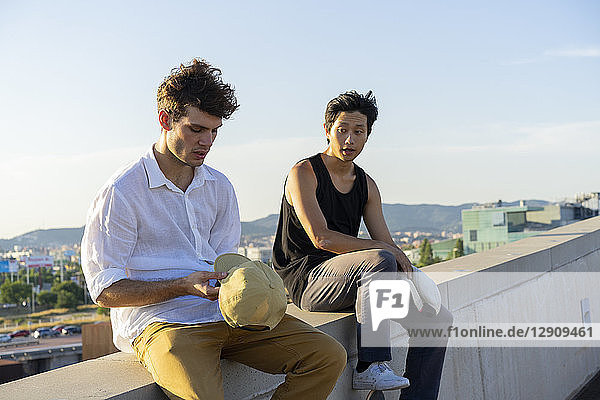 Two young men sitting and talking on a wall