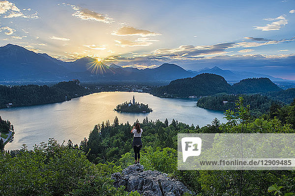 Slovenia  Bled  Young woman taking picture of Bled island and Church of the Assumption of Maria at sunrise