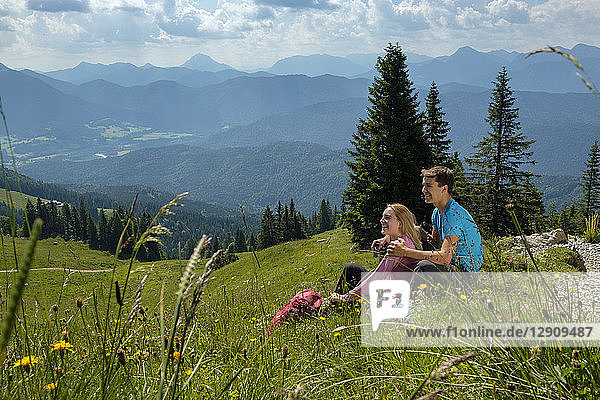 Germany  Bavaria  Brauneck near Lenggries  happy young couple having a break sitting in meadow in alpine landscape