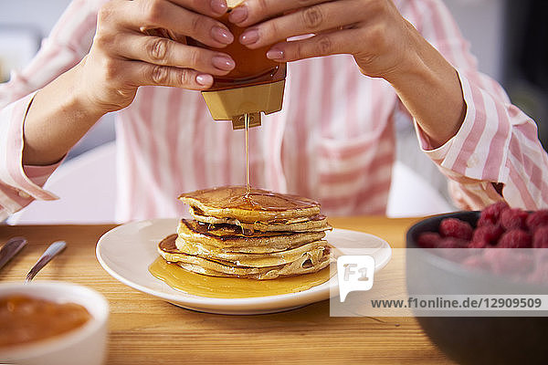 Young woman having sweet pancakes for breakfast  close up