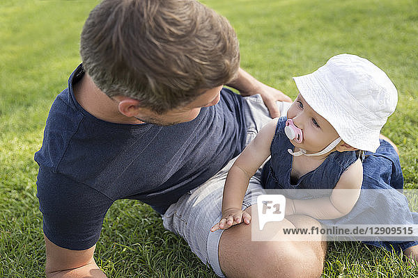 Father with little daughter on meadow