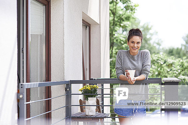 Young woman drinking morning coffee on the balcony
