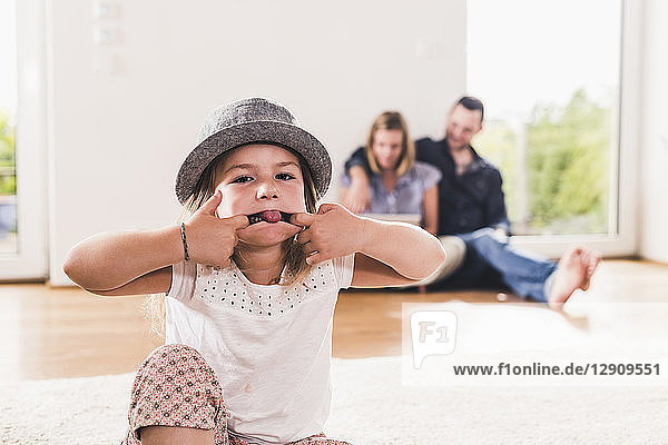 Little girl with hat having fun at home  parents using laptop in background
