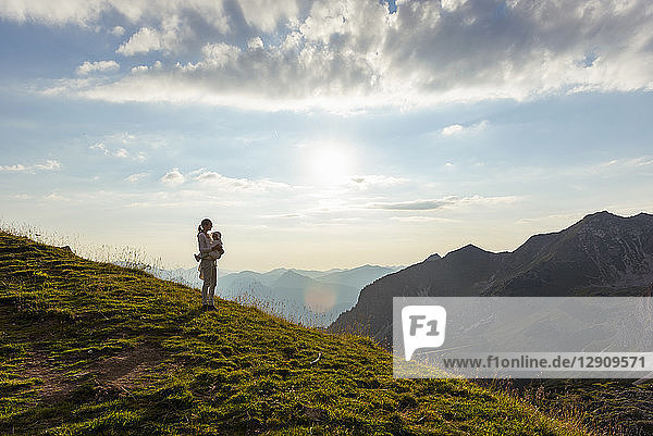 Germany  Bavaria  Oberstdorf  mother and little daughter on a hike in the mountains looking at view at sunset