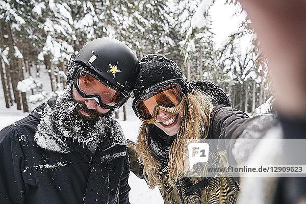 Selfie of smiling couple in skiwear in winter forest