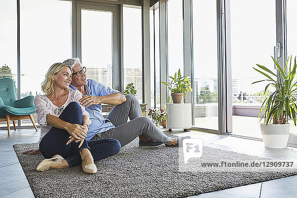 Smiling mature couple relaxing at home looking out of window