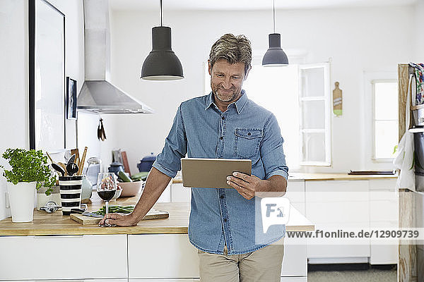 Mature man in his kitchen reading recipe on his digital tablet