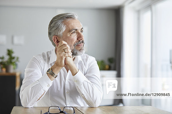 Portrait of pensive mature man at home