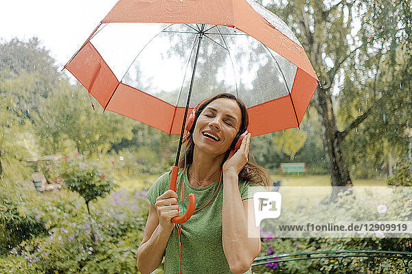 Happy mature woman standing in rain under umbrella listening to music with headphones