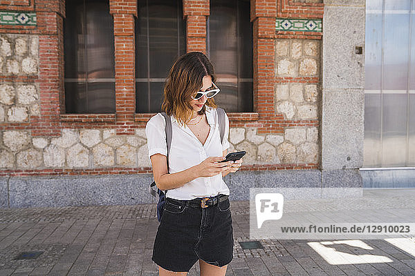 Young woman sight seeing in Madrid  using smartphone