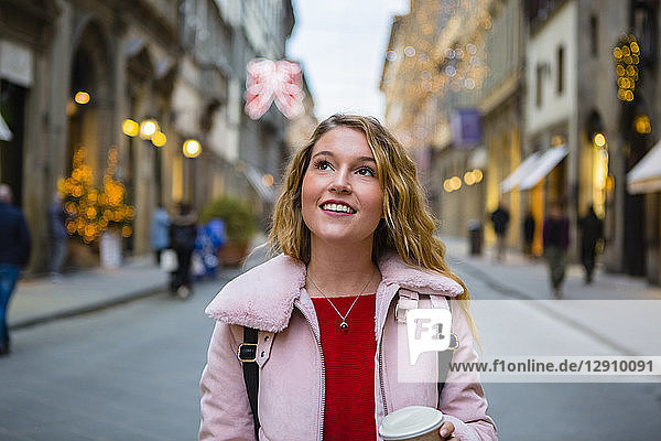 Italy  Florence  portrait of smiling tourist walking with coffee to go on the street in the evening