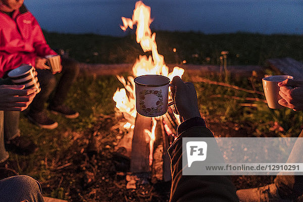 Hand of person holding tea cup  group of people sitting at a camp fire