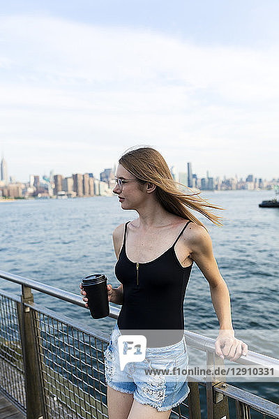Young woman looking over East River  holding cup of coffee