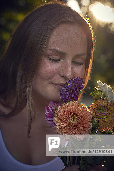Young woman smelling bunch of flowers